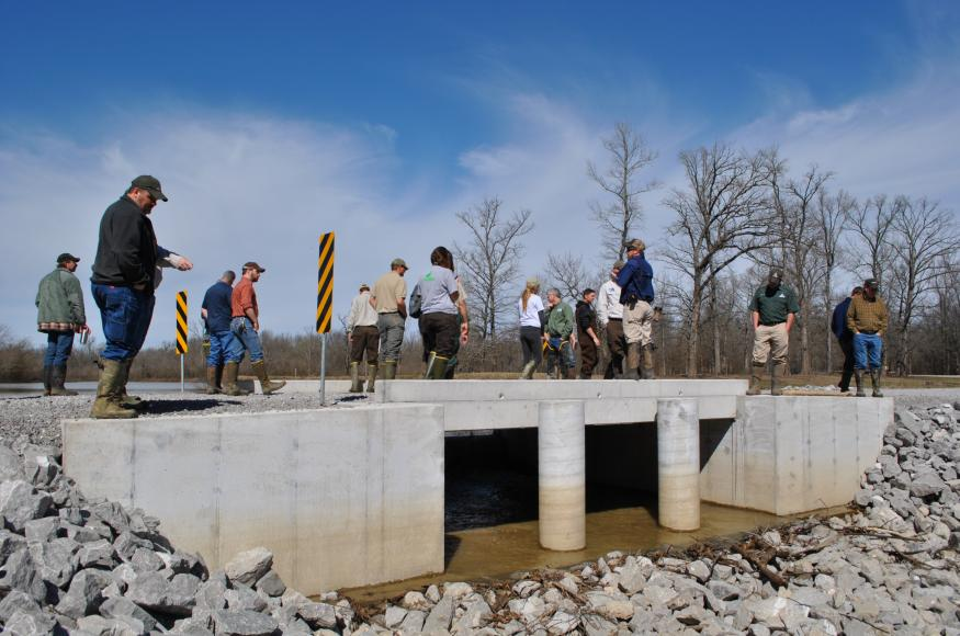 A group of people stand on a road with a box culvert underneat