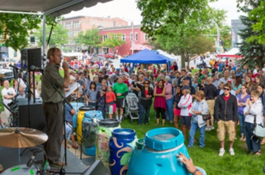 people gathered at an outdoor event for arbor day with a stage.